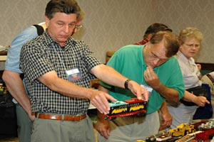 At a club-sponsored train show, a savvy shopper considers purchasing a Lionel Auto Loader car.